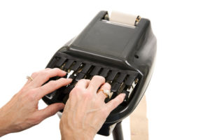 Closeup of a court reporters hands typing on a stenograph machine. Isolated on white background.